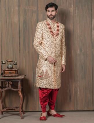 Beige embellished groom sherwani with red dhoti