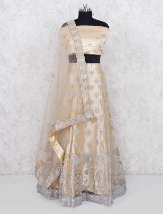 Beige hue net party wear semi stitched lehenga choli