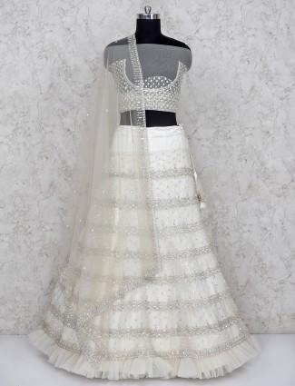Off white net semi stitched frill lehenga choli