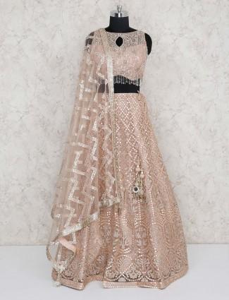 Peach hue net fabric lehenga choli for wedding