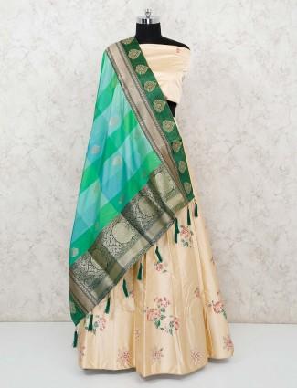 Semi stitched cream silk lehenga with green silk dupatta